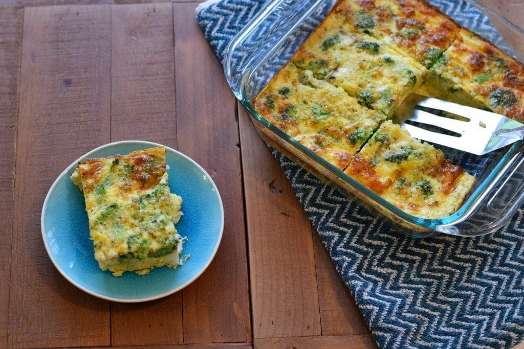 piece of egg bake beside a healthy pan of broccoli egg bake