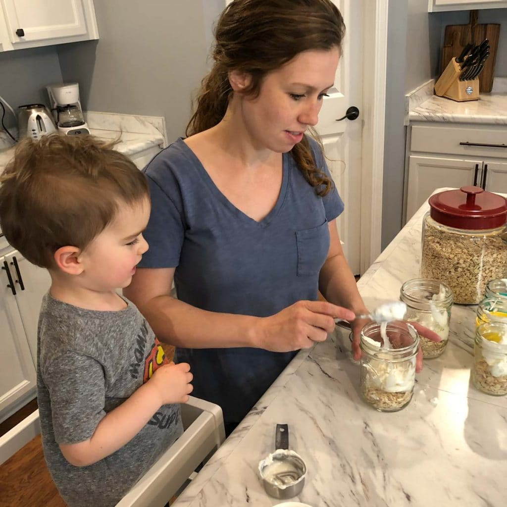 toddler cooking in toddler learning tower with his mother