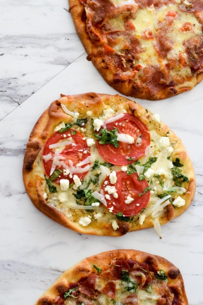 Naan bread pizza with tomatoes and spinach
