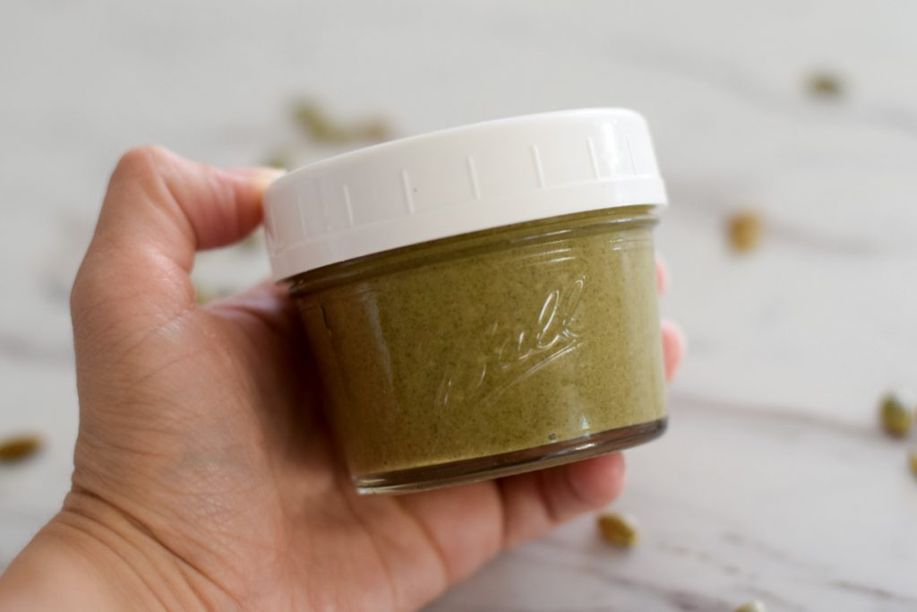small jar of peptia seed butter with pumpkin seeds lying on the table