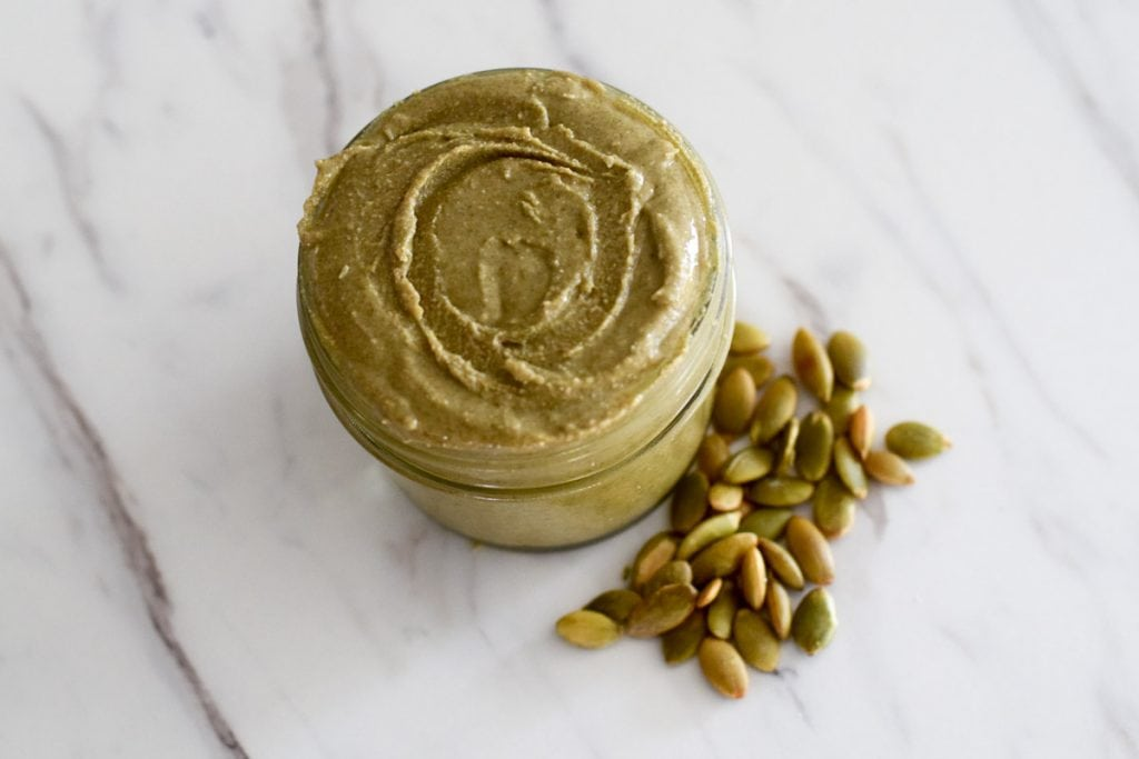pumpkin seed butter in glass jar with peptias beside it