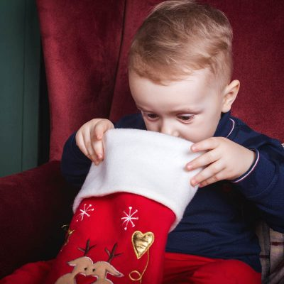 toddler pulling stuffers out of Christmas stocking