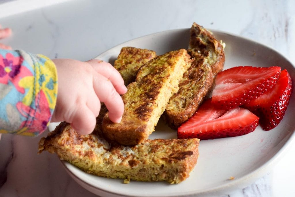 baby reaching for baby french toast and strawberries