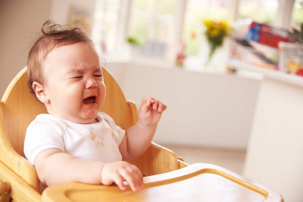 toddler in high chair throwing food