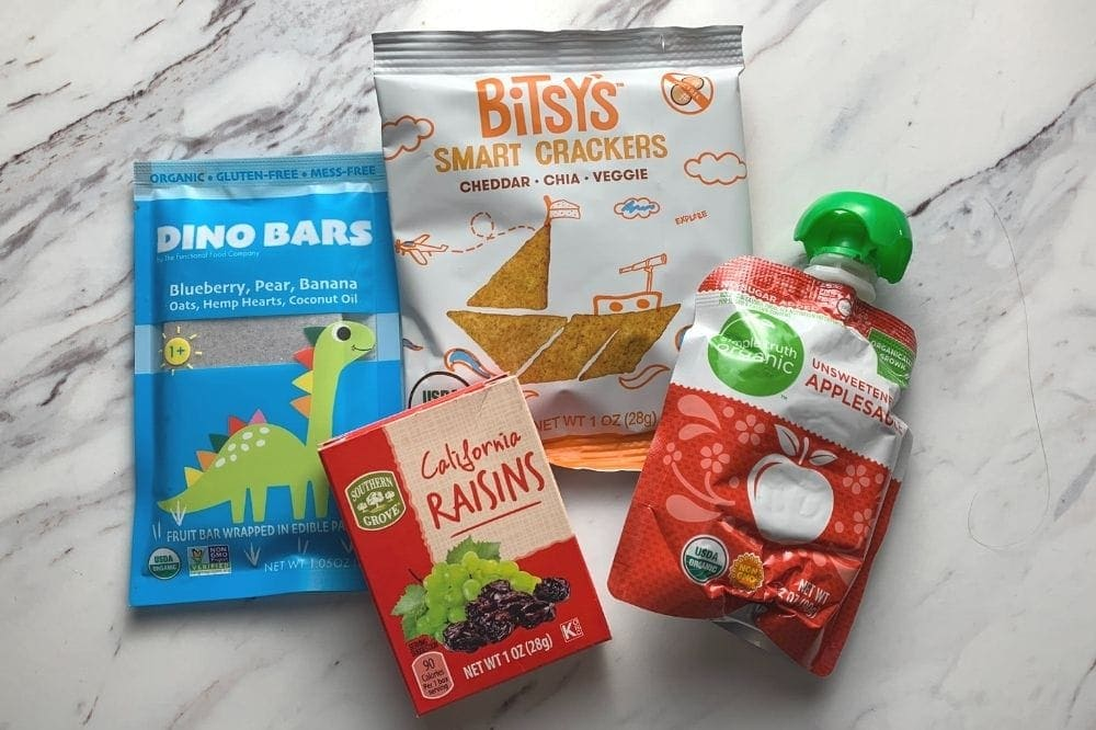 4 healthy store bought snacks for toddlers including crackers, raisins, dino bars, and apple sauce