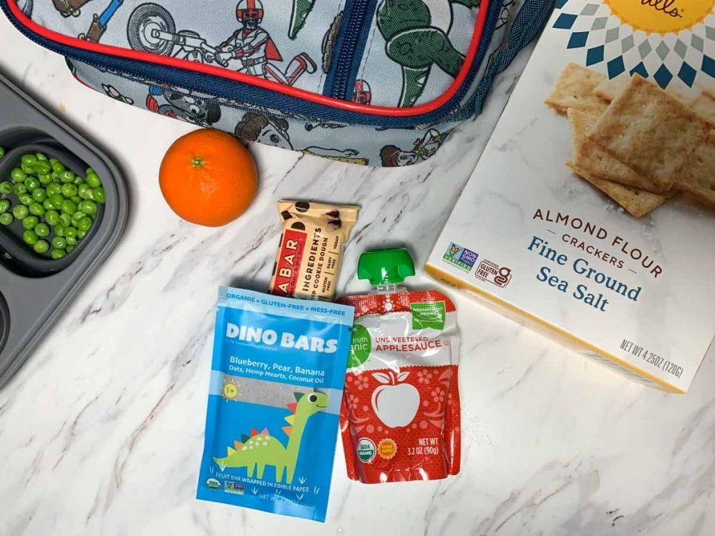 healthy toddler snacks for daycare shown in photo including energy bars, healthy crackers, and peas.